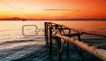 Primitive wooden pier at sunset