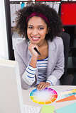 Smiling female photo editor at office desk