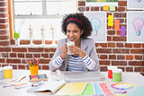 Portrait of female interior designer with coffee cup at desk