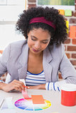 Female designer with color samples at desk