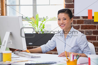 Smiling young woman working at desk
