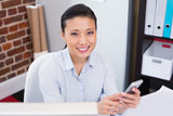 Smiling female executive text messaging in office