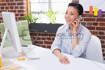 Female executive using mobile phone at desk