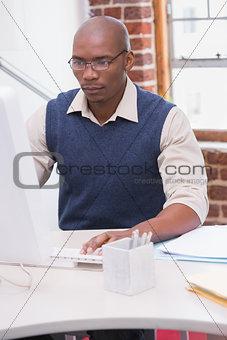 Serious businessman looking at computer monitor