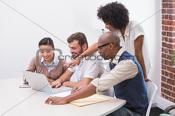 Concentrated business team using laptop in meeting