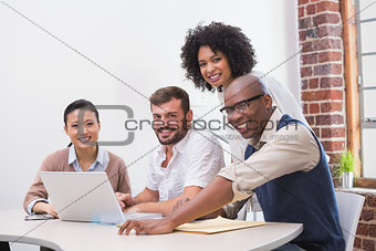 Creative business team using laptop in meeting