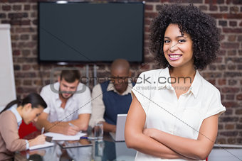 Smiling businesswoman with colleagues in background at office