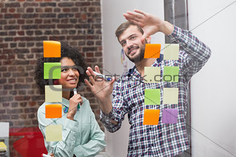 Business team looking at sticky notes on window