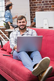 Man using laptop on couch in office