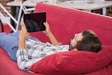 Casual man using digital tablet on couch