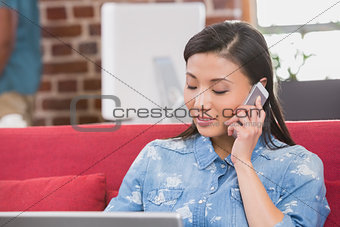 Casual woman using laptop and mobile phone on couch