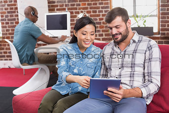 Casual colleagues using digital tablet on couch