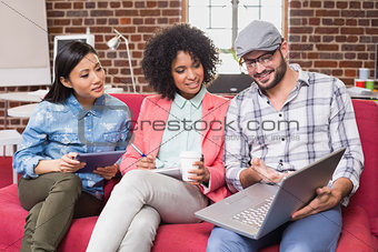 Casual colleagues using laptop on couch