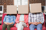 Team sitting on couch with boxes over heads