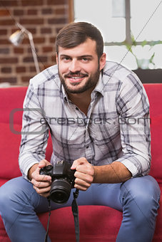 Portrait of casual photo editor holding camera