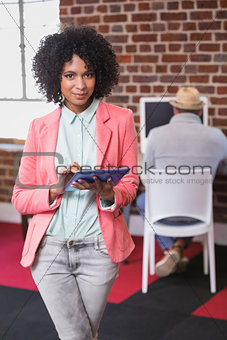 Casual woman using digital tablet with colleague behind in office