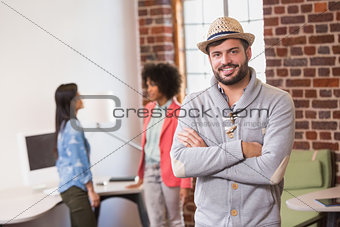 Man with arms crossed and colleagues behind in office