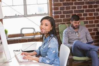 Portrait of smiling female executive using computer