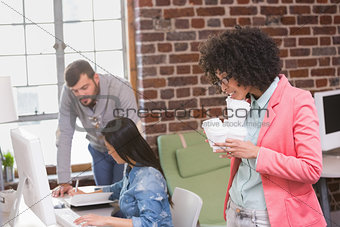 Executives using computer with woman holding disposable cups