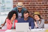 Creative team using laptop in meeting