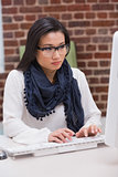 Serious casual young woman using computer