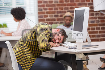 Casual man resting head on computer keyboard