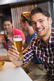Young man holding pint of beer