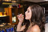 Pretty brunette drinking a shot