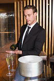 Handsome man pouring glass of champagne