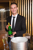 Handsome man showing champagne bottle