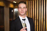 Handsome man holding flute of champagne
