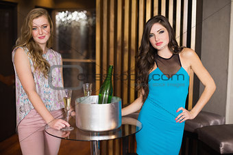 Attractive friends smiling by champagne