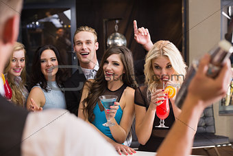 Attractive friends being served cocktails
