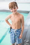 Cute little boy standing poolside