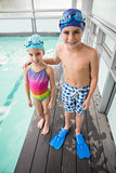 Cute little siblings standing poolside