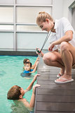 Pretty swimming coach showing boy his time
