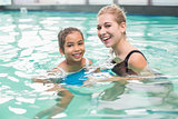Cute little girl learning to swim with coach