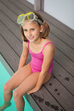 Cute little girl sitting poolside