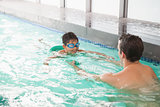 Cute swimming class in pool with coach