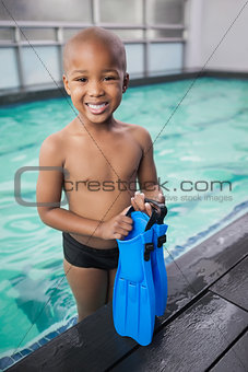 Little boy holding flippers by the pool