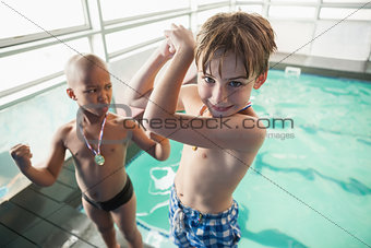 Little boys standing by the pool with medals