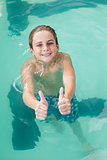 Little boy showing thumbs up in the pool