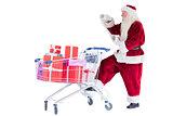 Santa pushes a shopping cart while reading