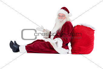 Santa sits leaned on his bag and has no clue