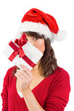 Festive woman looking at camera holding a gift