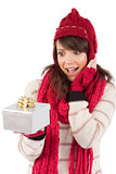 Surprised young woman holding a wrapped gift