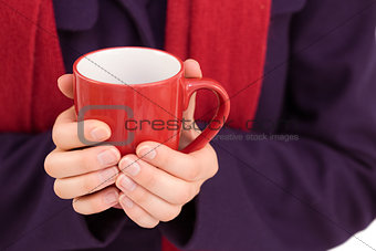 Close up of a woman in warm clothing holding mug