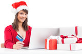 Festive brunette shopping online with laptop