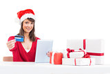 Festive brunette shopping online with tablet pc