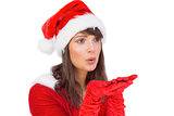 Pretty brunette in santa outfit blowing over hands
